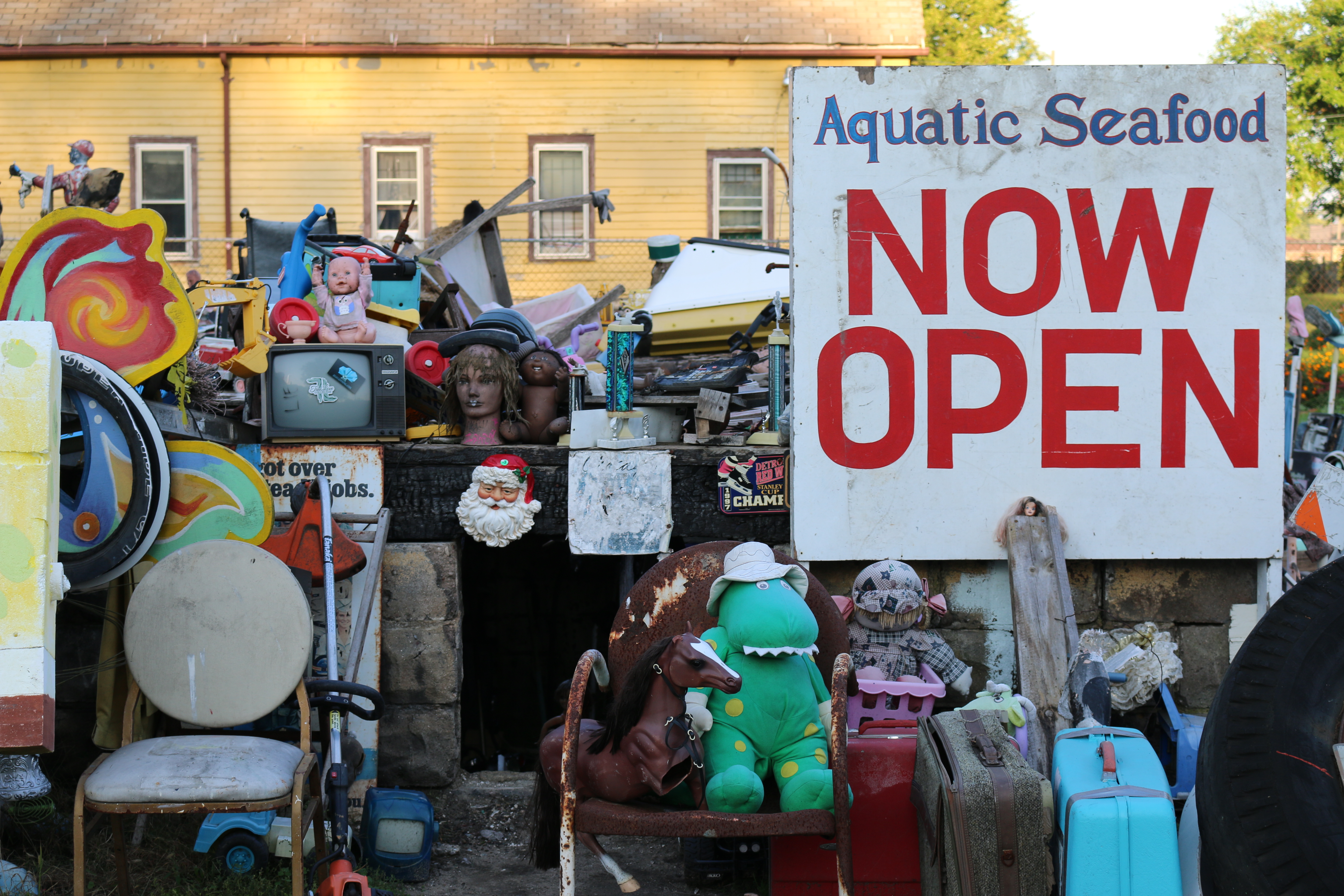Large Now Open Aquatic Seafood sign with large cardboard Sponge Bob Squarepants standing on a chair with several random sea animal toys.