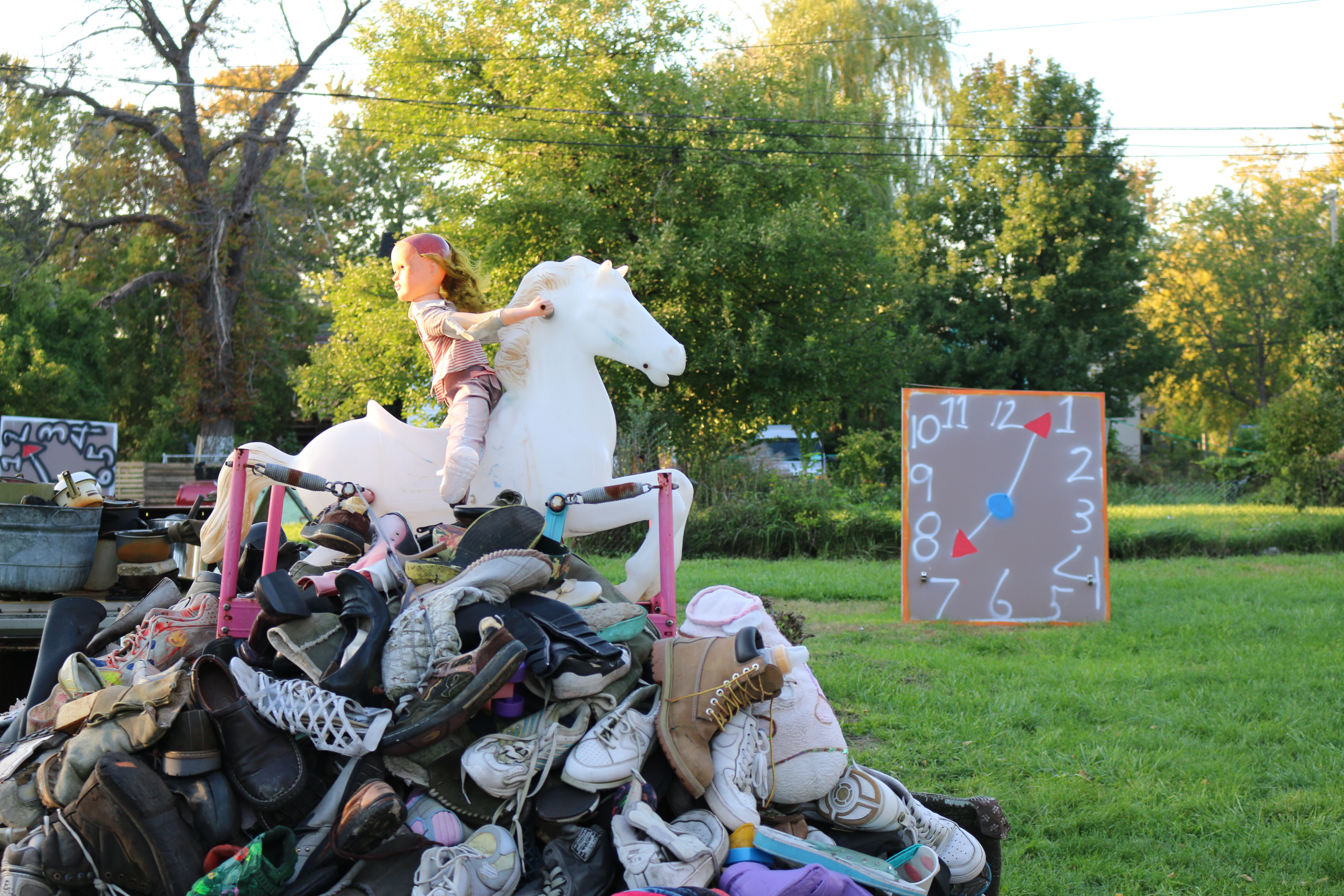 Close up of baby doll riding a white unicorn toy on top of pile of toys.