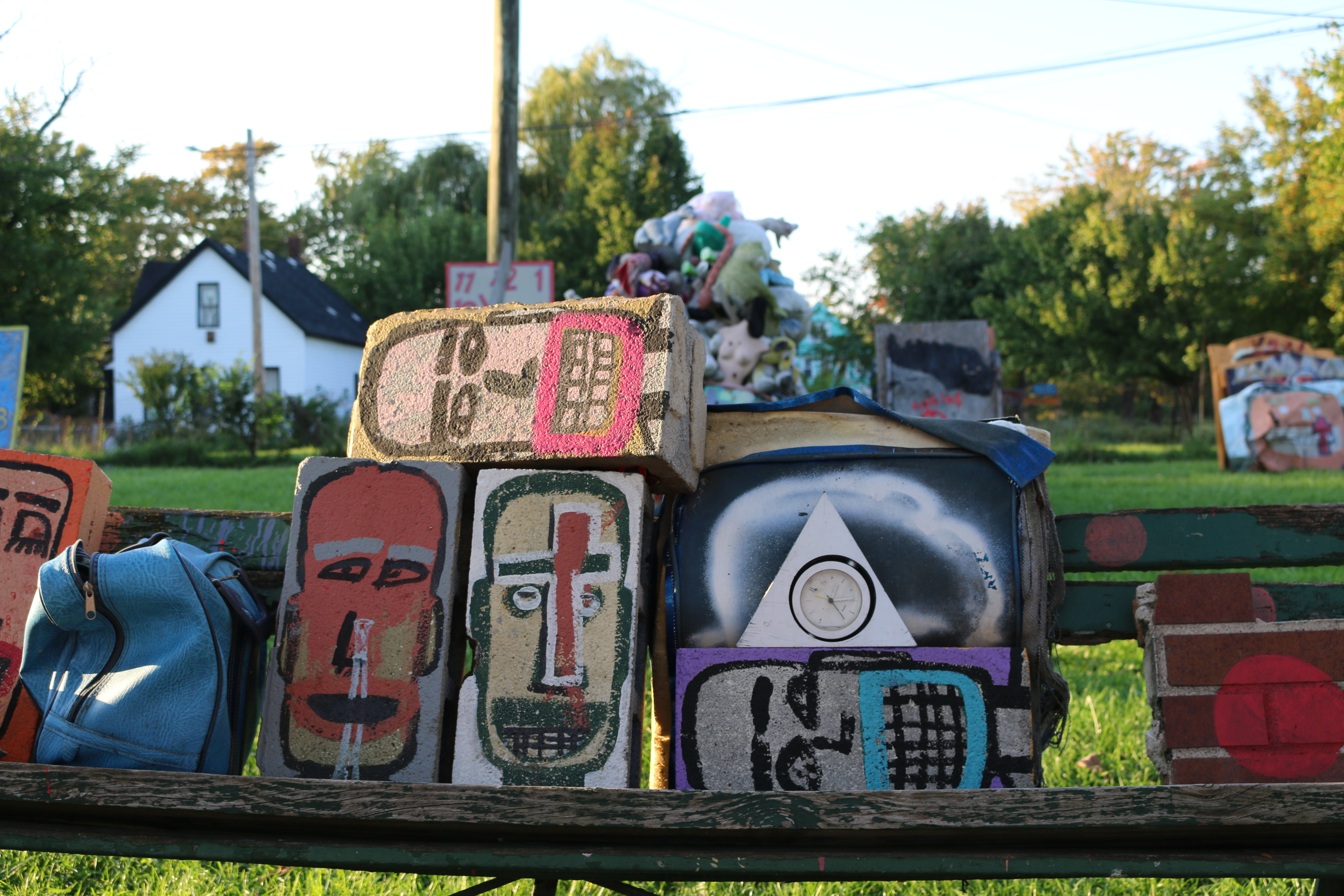 Large faces painted on blocks and car hood.