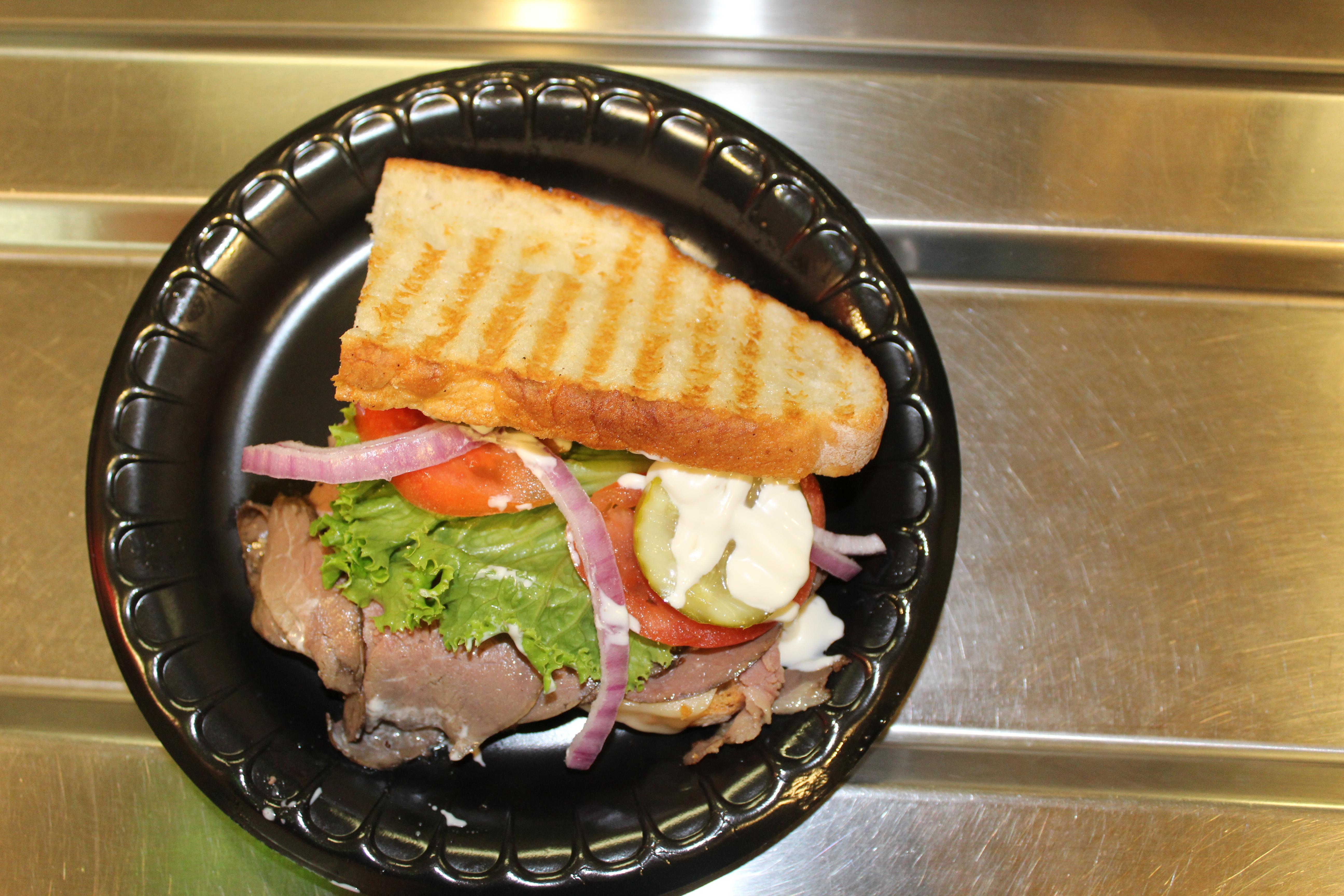 Panini sandwich on a black plastic plate.