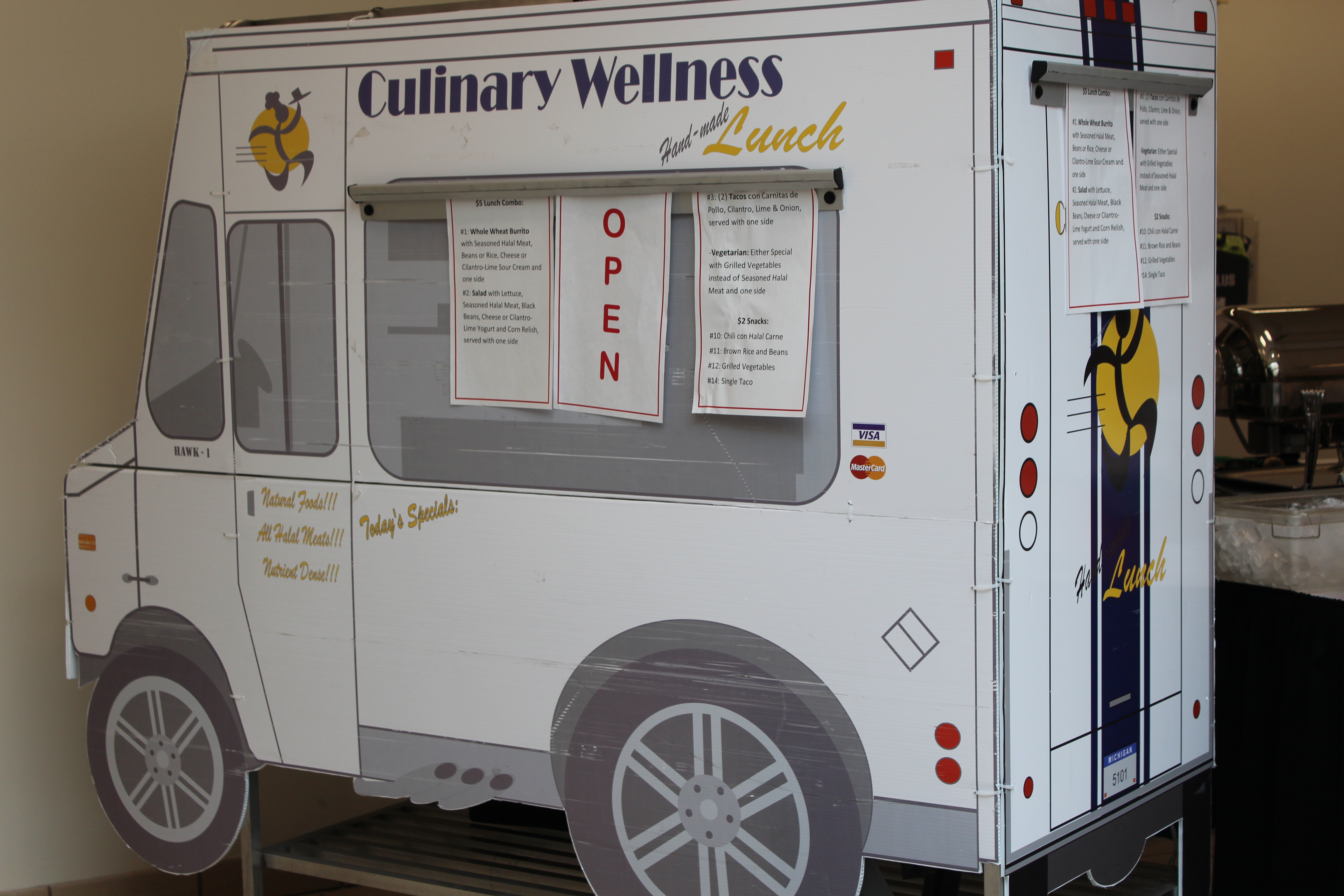 White cardboard food truck with menus on the drawings of windows.