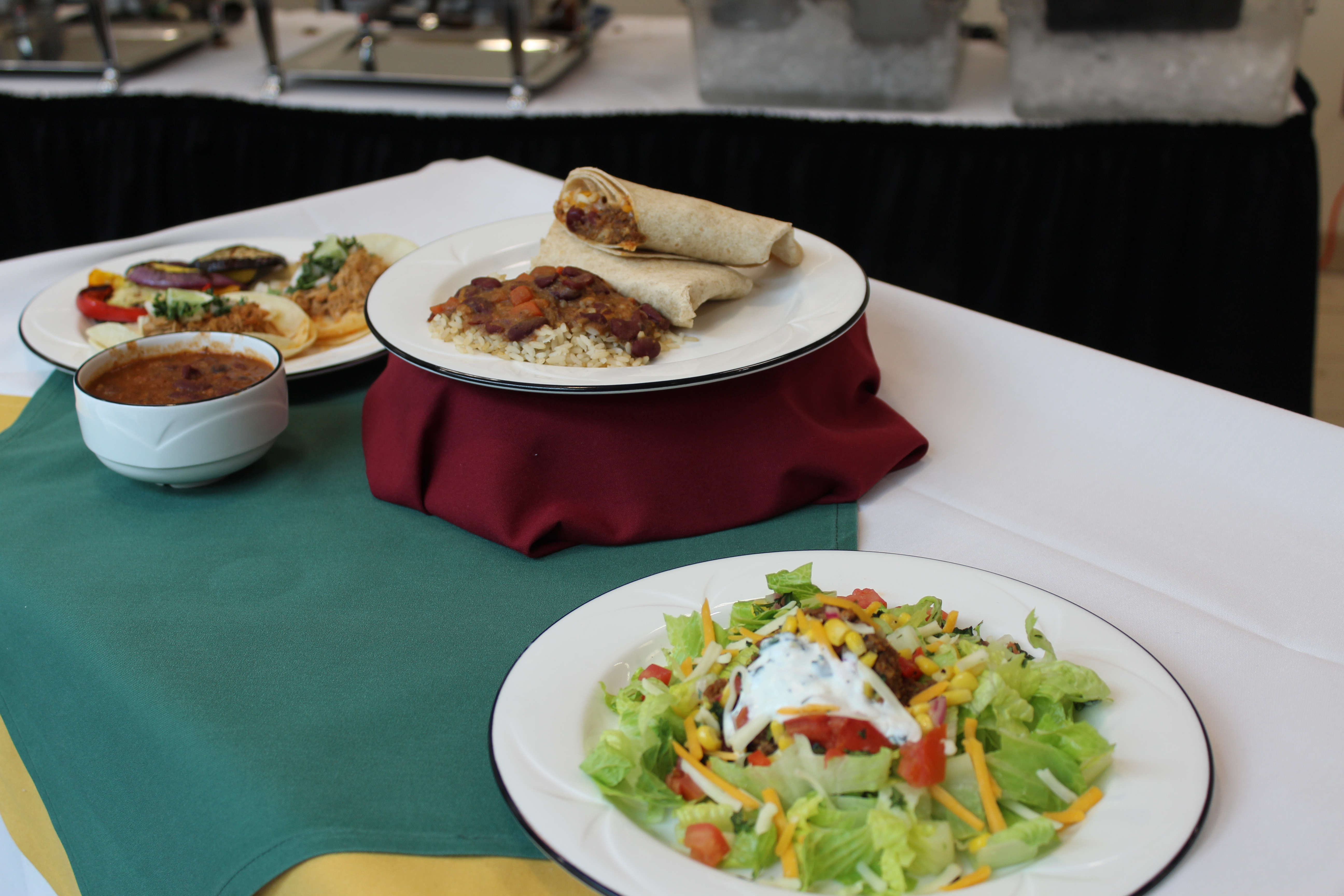 Three plates on a white table cloth with a green cloth napkin. One plate has a salad, the middle plate has burritos, and the third plate has tacos with a bowl of chili.