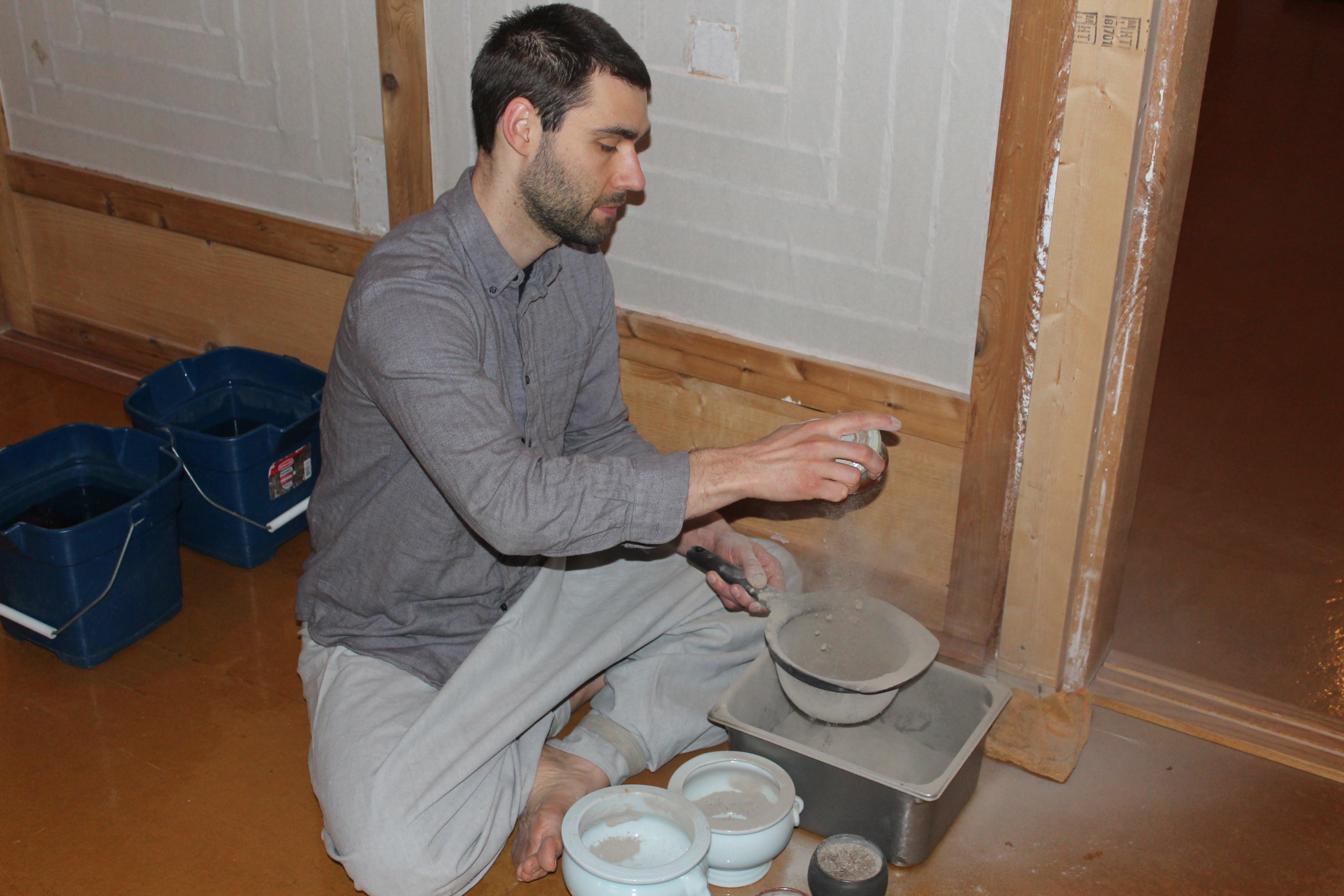 Majin Luke Niewiadowski refilling incense bowls.