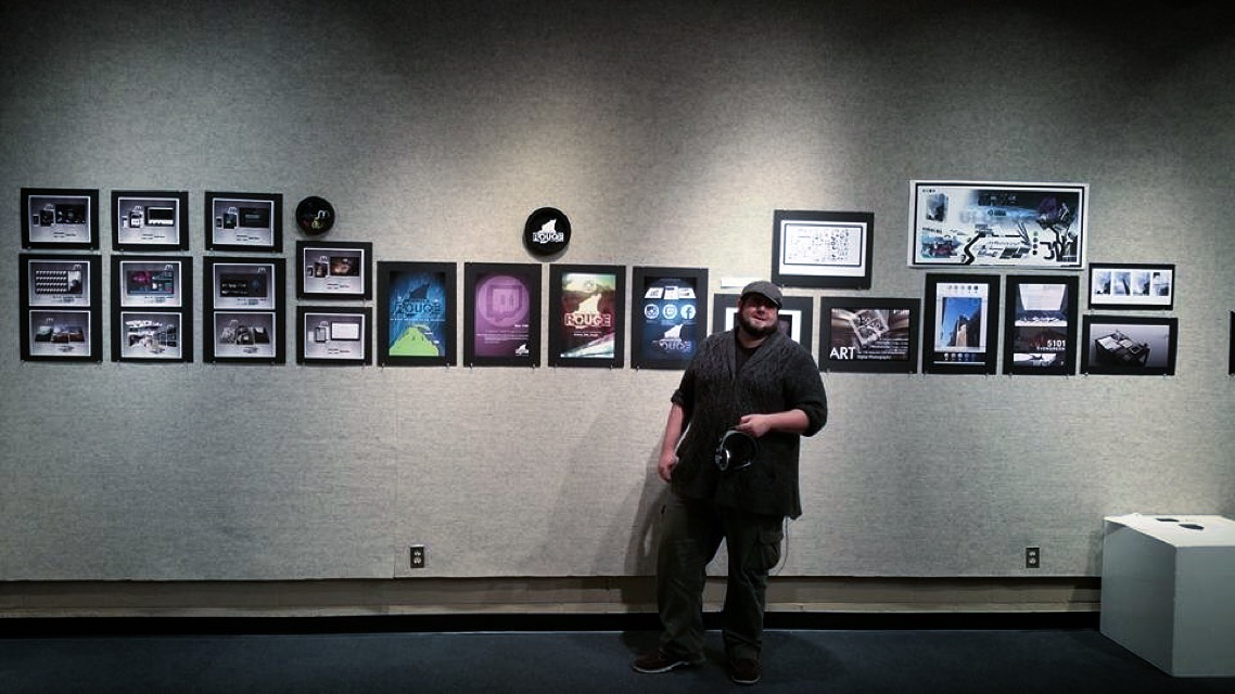 Jerry Moore stands next to several prints of his digital artwork, displayed on the wall behind him.