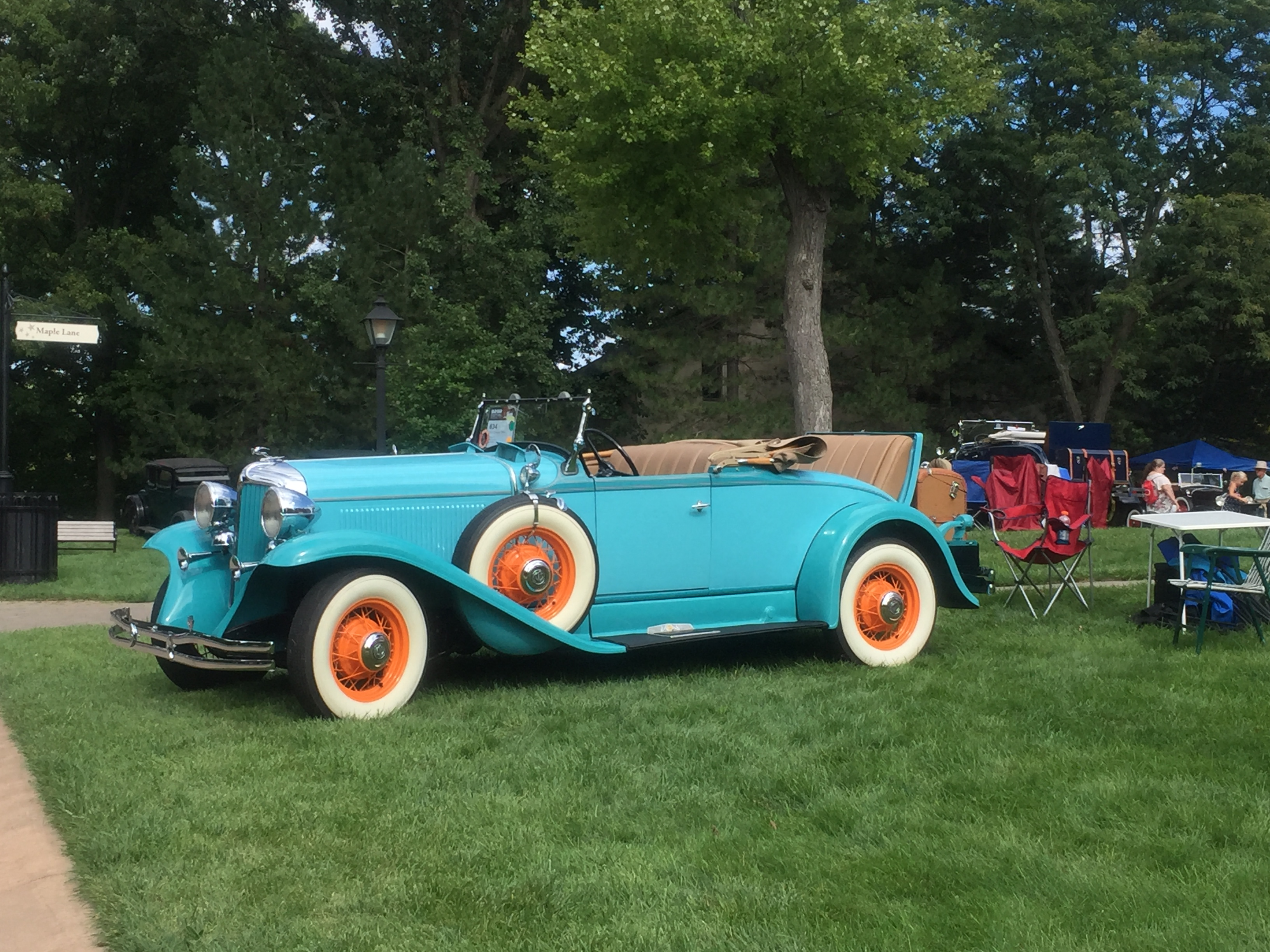 Photo of classic convertible 1930s car painted aqua blue with whitewall tires.