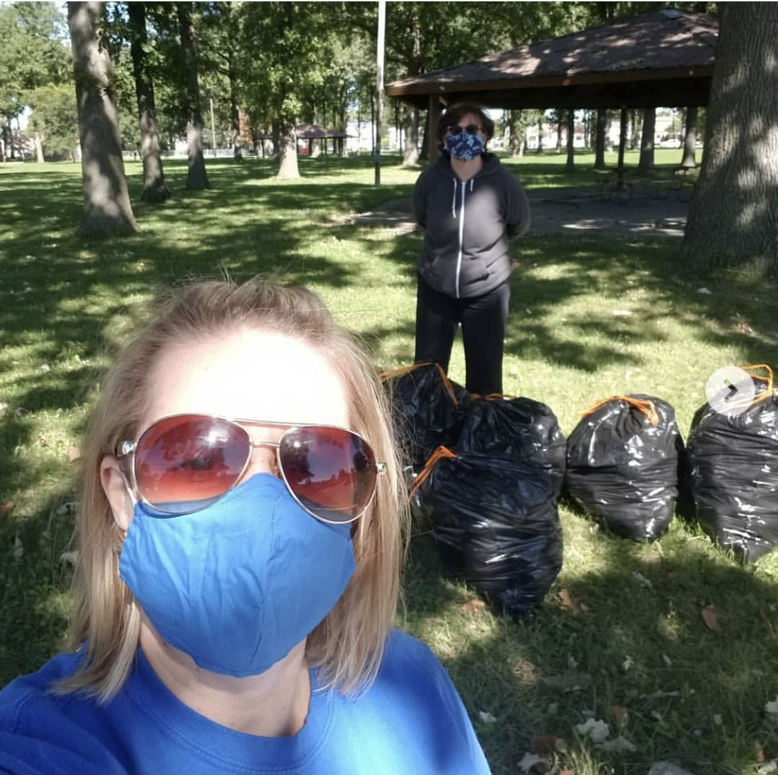 Mandy Earl, student activities office associate, posing with a student on HFC Volunteer Day at Youth Center Park