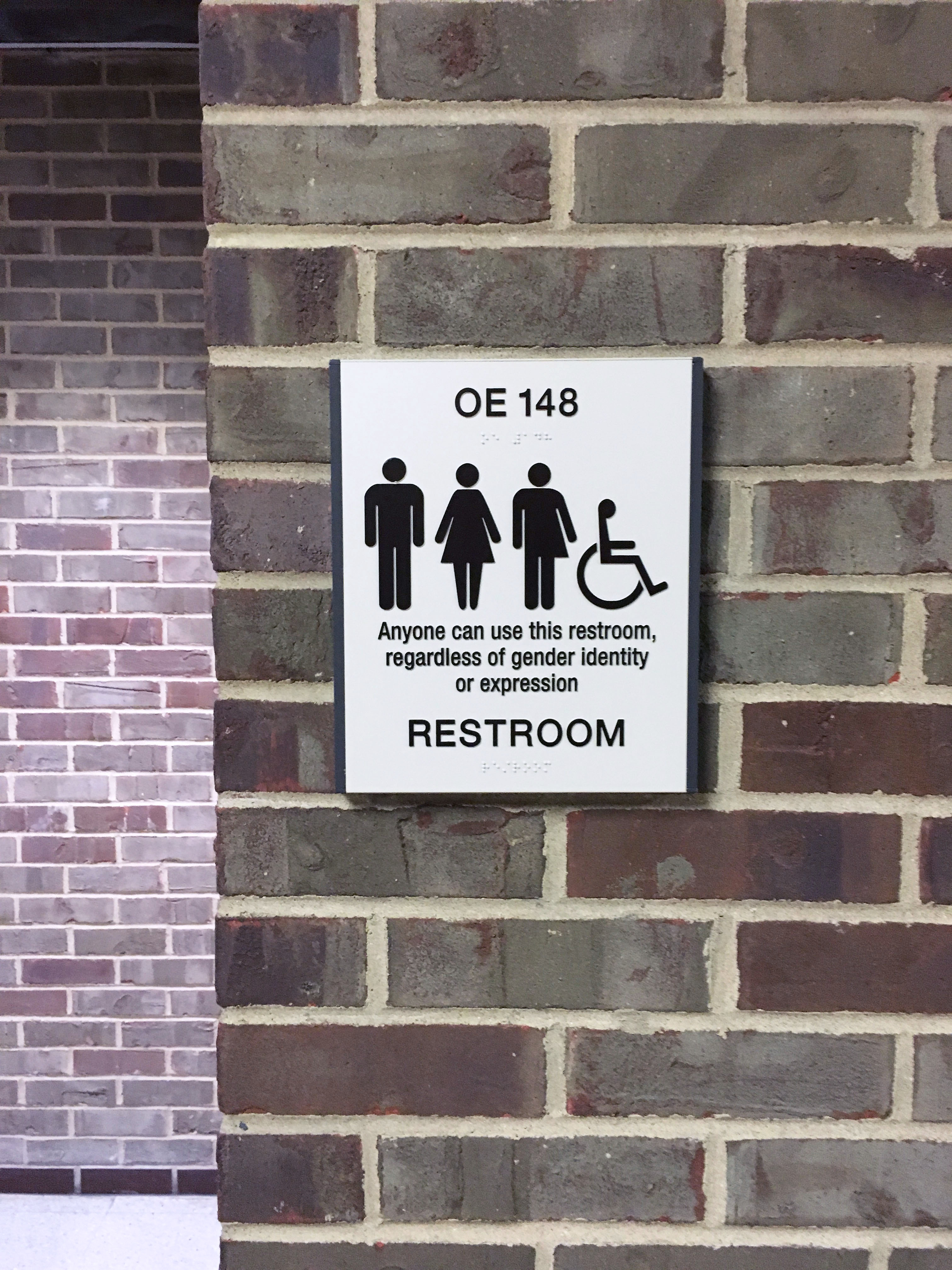 """A brick wall displays a sign that has four symbols: a stick figure in pants typically denoting the male gender, a stick figure in a dress typically denoting the female gender, a stick figure that is wearing pants on one side and a dress on the other, and the stick figure denoting accessibility. The text on the sign notes it is a restroom and, """"anyone can use this restroom, regardless of gender identity or expression""""."""