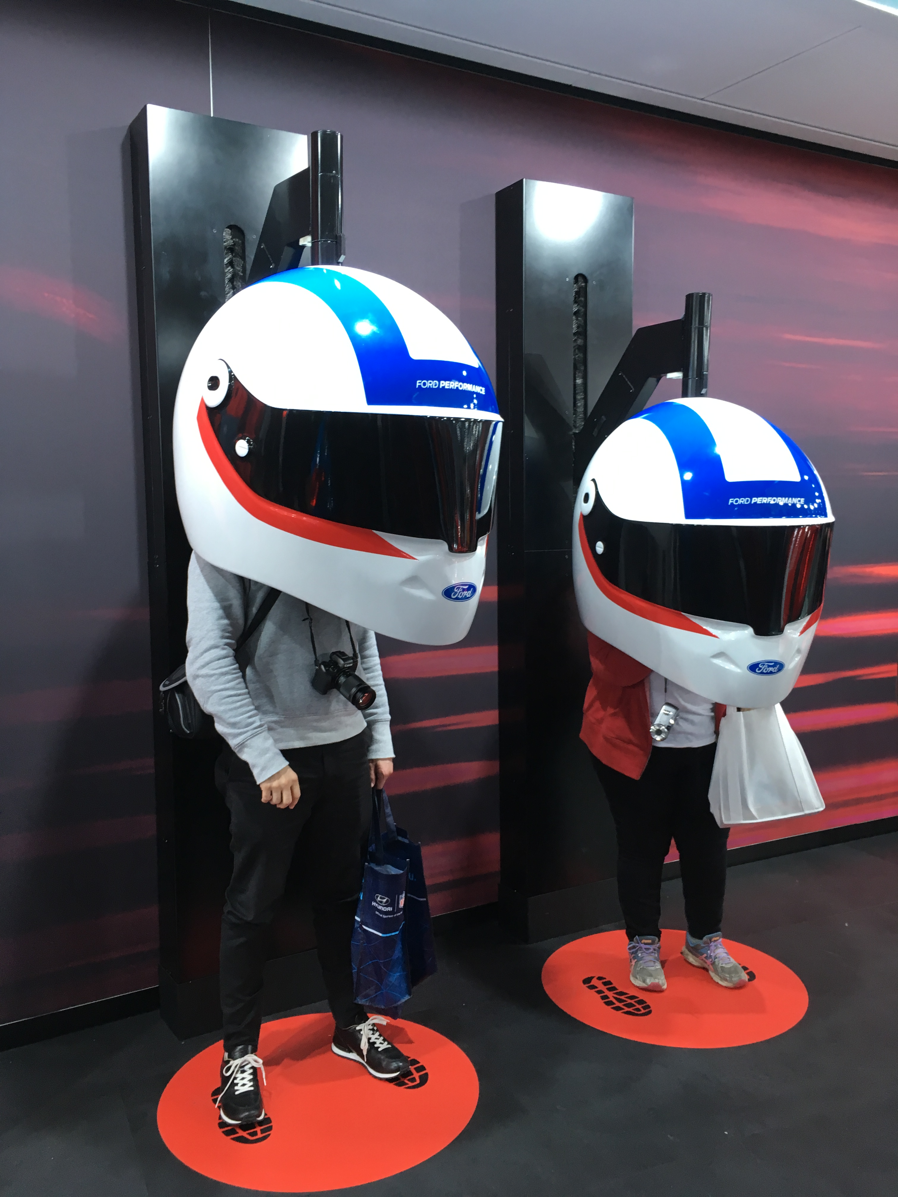 Giant racing helmets on two people at 2018 North American International Auto Show in Detroit