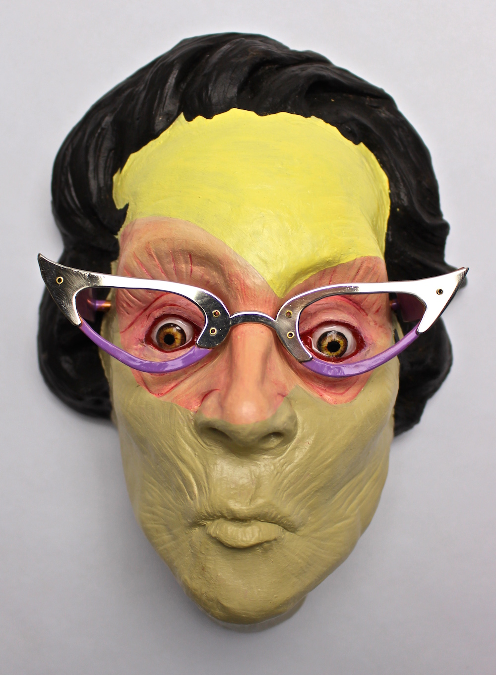 Luke Halling self-portrait mask with black hair and horn rimmed glasses