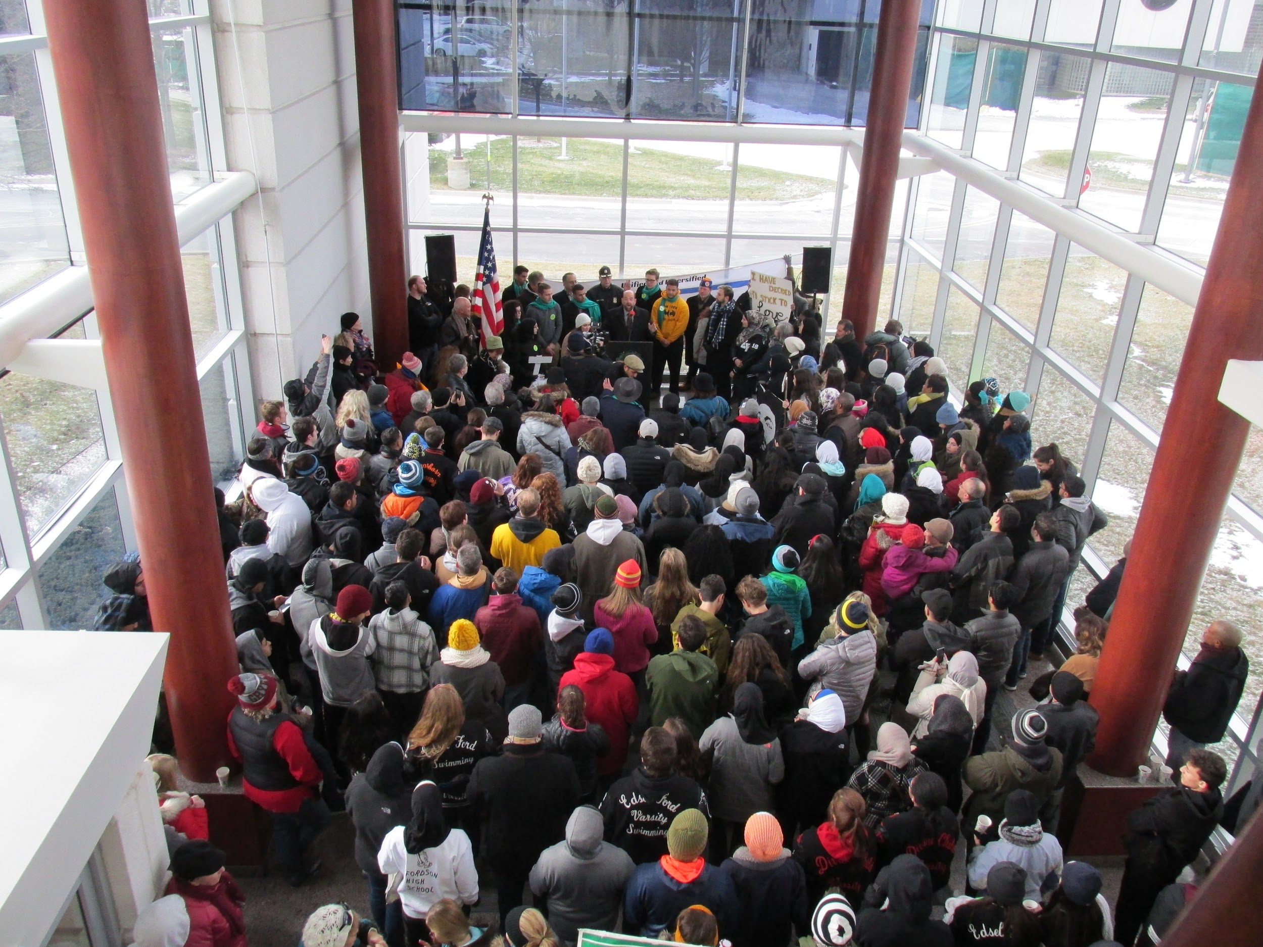 A top down view of roughly 100 people gathered in a lobby space. They stand in front of a podium where several people are standing.