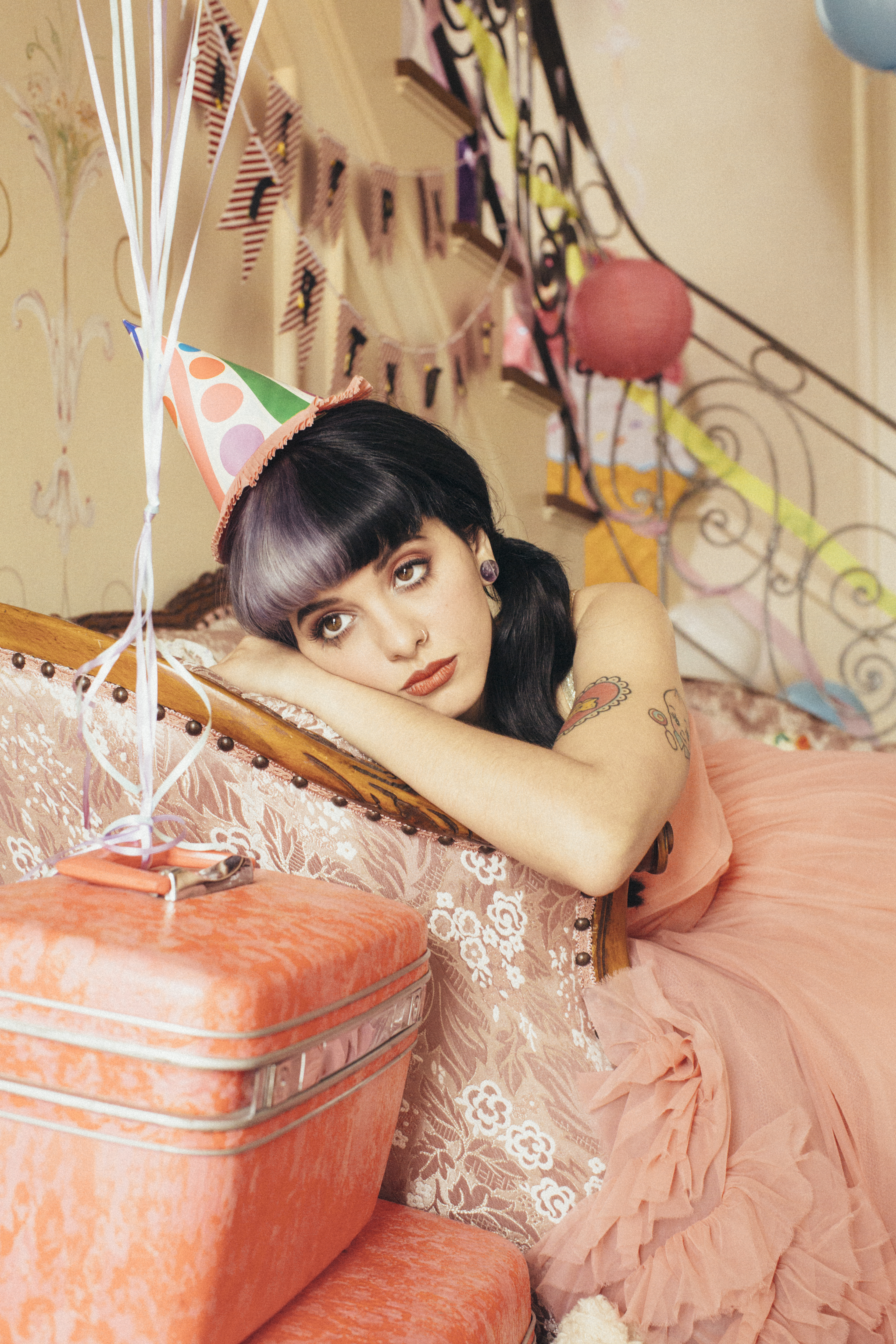 Melanie Martinez promotional photo wearing pink birthday dress with a birthday hat, but pouting.
