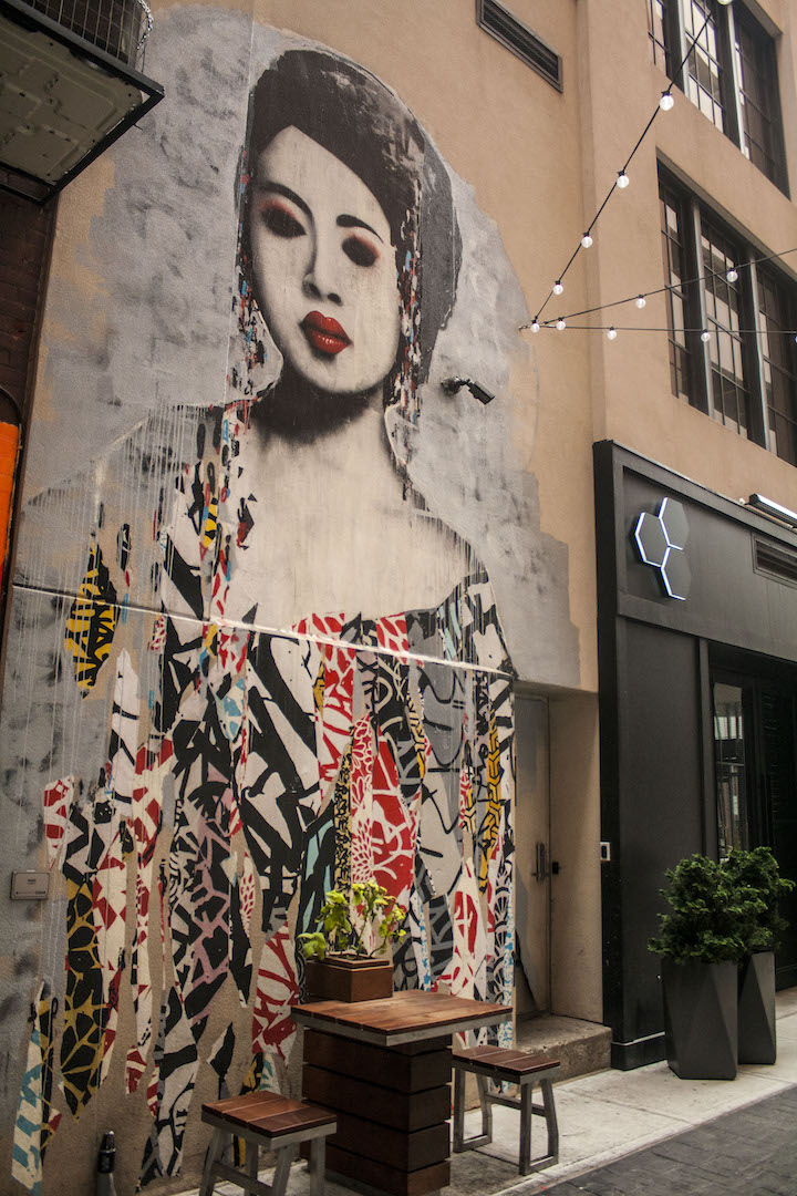 The brick exterior of a building has a large, detailed painting of an asian woman, who is depicted to be dressed in colorful strips, with elaborate patterns.