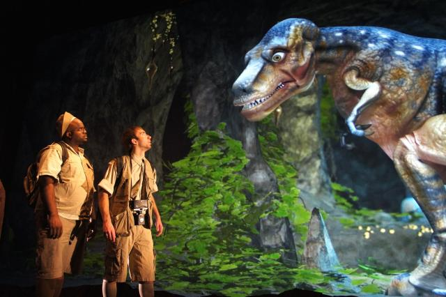 Two men in safari style gear gaze up at a rendered dinosaur. The dinosaur looks down at them.
