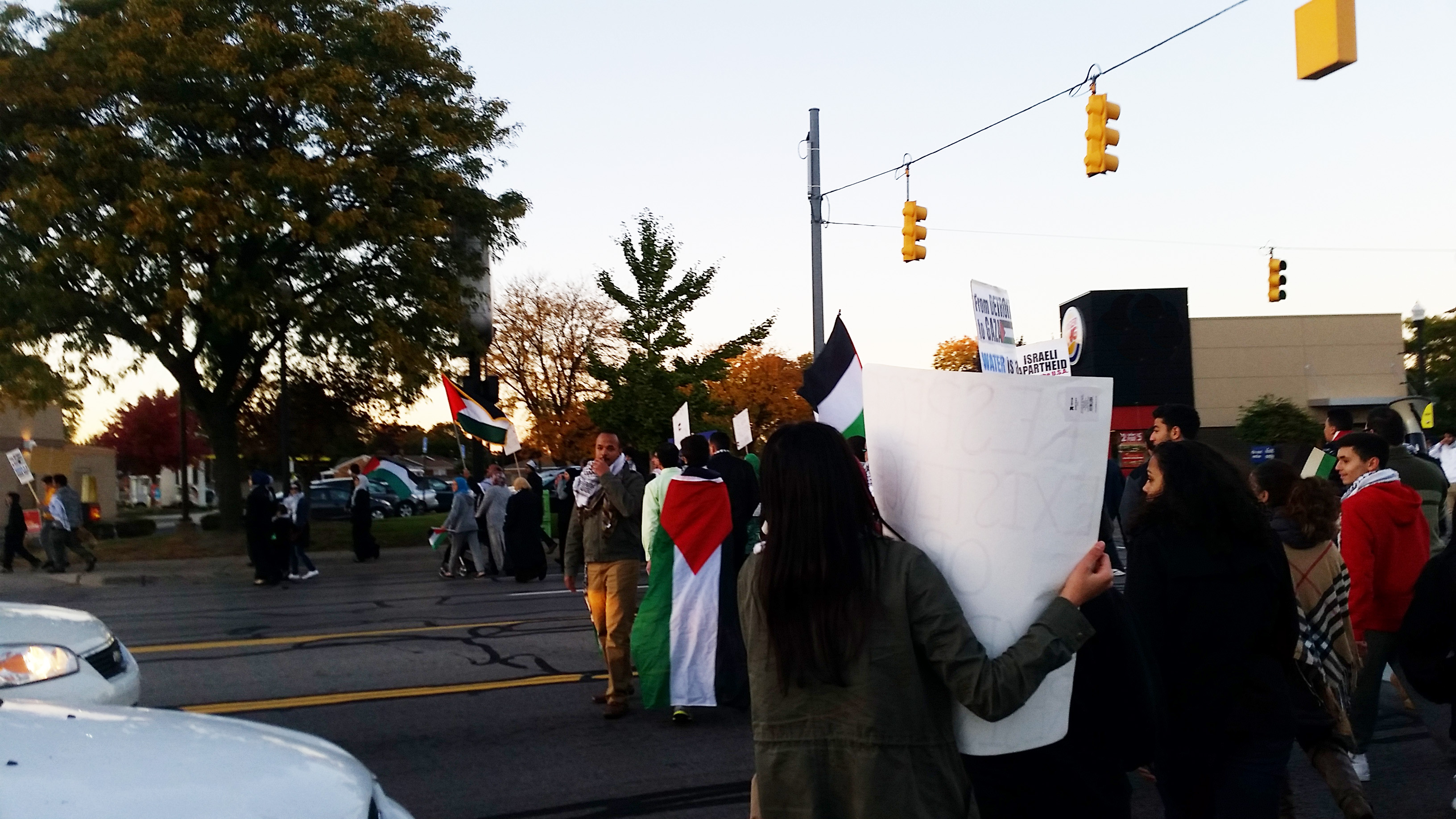A row of protesters move across a street, holding signs and Palestinian flags.
