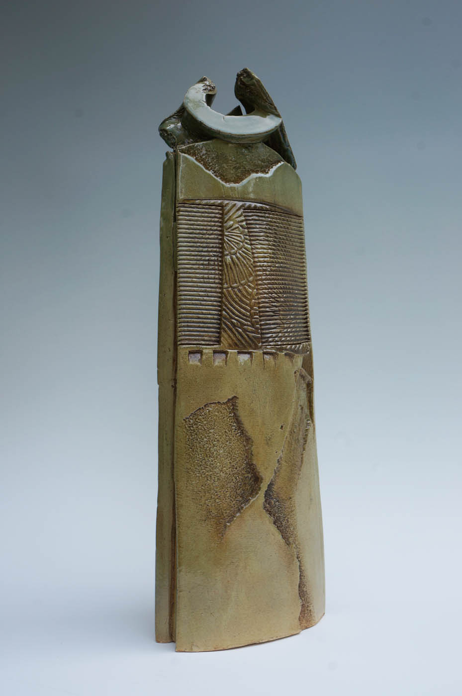 3D tall vase by Robert Piepenburg with earth tones and sculpted with grooves and designs.