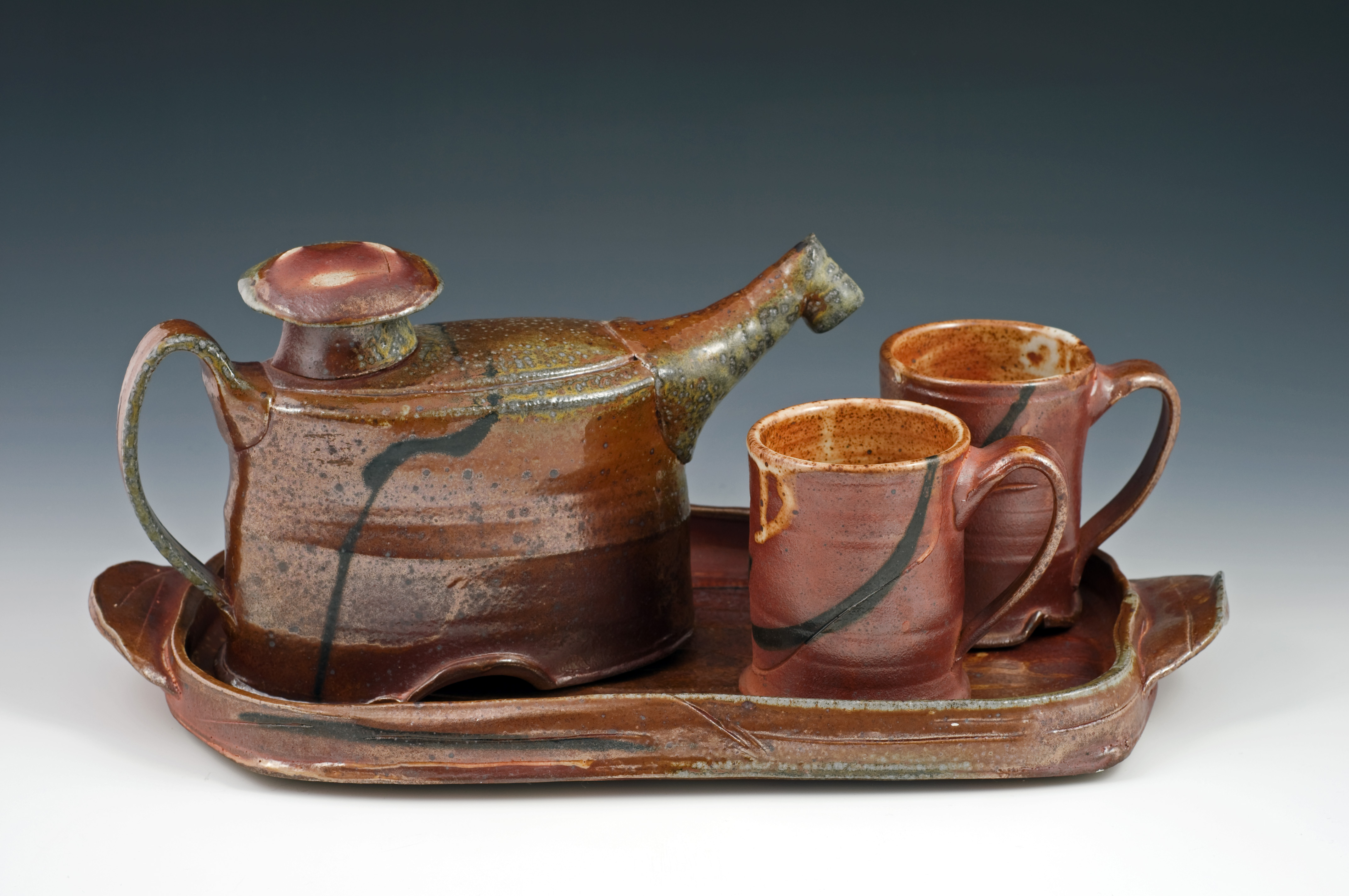 Glazed clay tea cups and pitcher on a tray by Sandra Dalton-Shaughnessey.