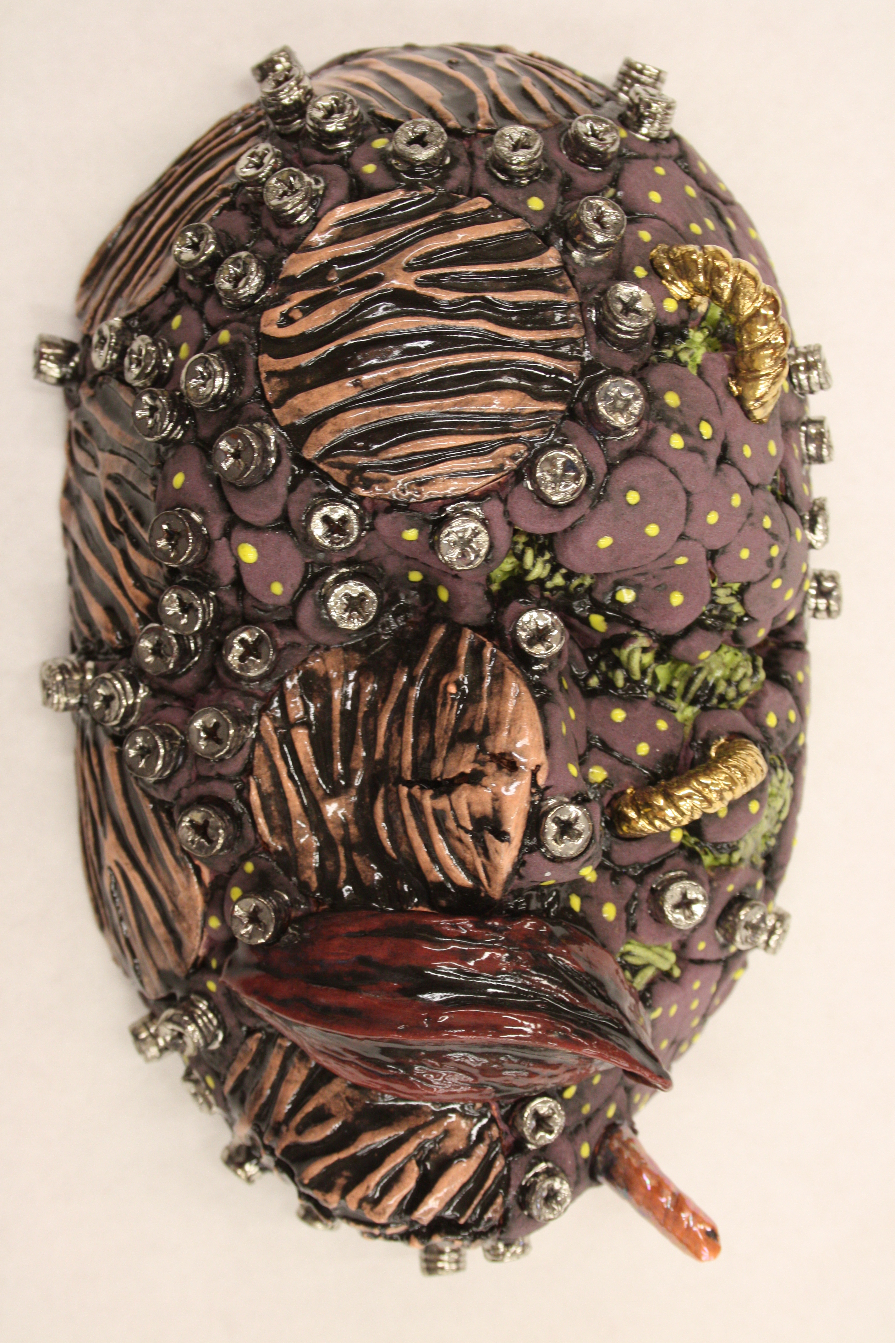 Clay mask covered in branches and organic looking pods by Steve Glazer.