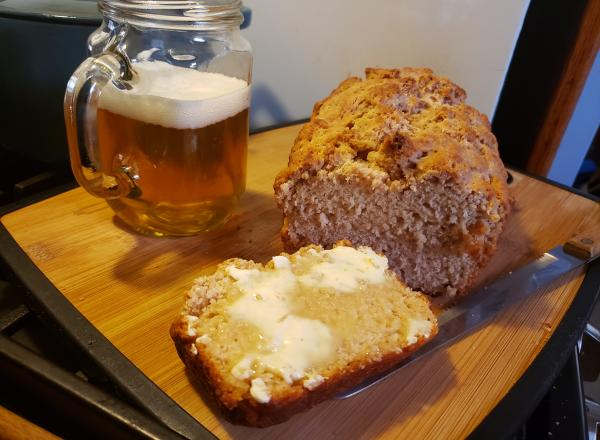 Photo of beer bread with a glass of beer on a cutting board