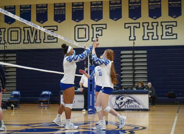 Hawks volleyball players giving each other high fives