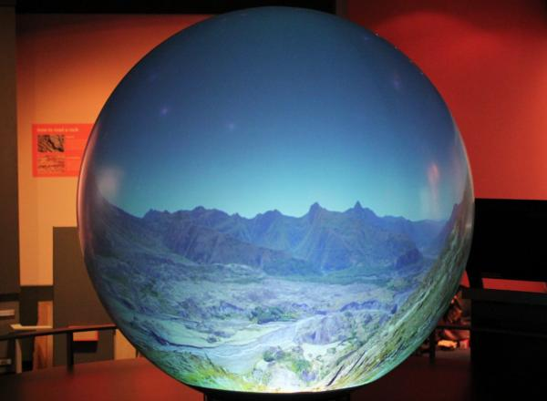 Image of a working Magic Planet device showing a mountain landscape photograph