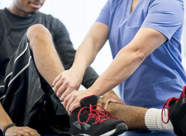 Image shows an athletic trainer working on an athlete