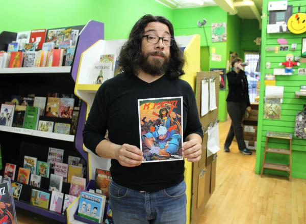 Image shows Saladin Ahmed holding a copy of Ms. Marvel #13 at Green Brain Comics