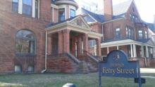 The Victorian homes of The Inn of Ferry Street. Older brick homes, stylized with sharp angles and ornate details. The sign of for the Inn is place in the yard.
