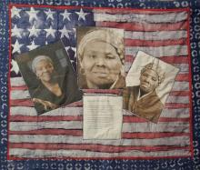 A small quilt hangs on a wall. It is an American flag that has been overlaid with three sepia tone photos of a middle aged African American woman. Below the center photo, we can see a letter that details thoughts about Harriet Tubman.