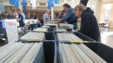 Photo shows several people looking through boxes of records