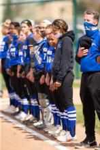 Hawks softball team lined up during national anthem.