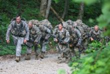Several soldiers clad in camo and gear trudge up a hill.