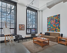 Interior photo of living room of the Artspace Lofts with large painting on the wall and floor to ceiling windows.