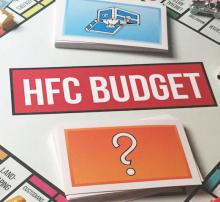 Monopoly style game board with items around board the names of college departments and HFC Budget with question mark cards under it.