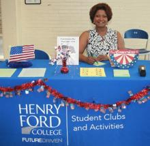 Image shows Student Activities Officer Cassandra Fluker sitting at a HFC booth