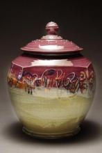 Photo of clay jar with a lid glazed purple and beige.