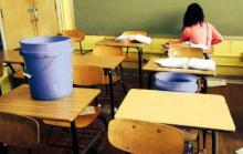 Buckets on desks catching leaks in a public school classroom