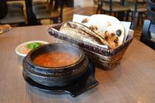 Photo of steaming clay pot of fahsah with pita bread.