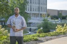Shahid Mohammad standing in front of the Liberal Arts building holding his film award.