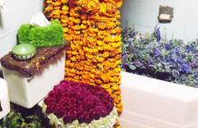 A bathroom has many flowers arranged to cover flat surfaces in an artful manner. A toilet seat has a cover made of bright, fuchsia colored flowers. The bathtub is filed with blue flowers. A shower curtain is made of many strands of orange mums strung together. A tissue box on the toilet's tank is covered in moss.