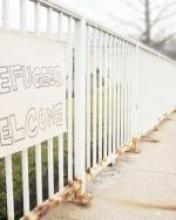 "A handwritten sign reading ""Refugees Welcome"" is posted on a white fence that extends into the distance."