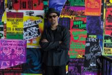 Photo of the artist Gary Simmons in front of his wall of colorful fly posters each with a Detroit theme.