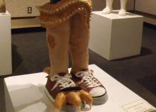 A ceramic sculpture of a set of legs, standing in red sneakers. One of the sneakers has three bird-like claws emerging from the toe of the shoe and one from the rear. A tentacle with many tiny teeth lining the edges has wrapped around the legs near the knees.
