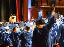 Students wearing the graduation caps in the graduating ceremony facing the stage.
