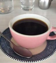 A cup of black coffee in a pink teacup.