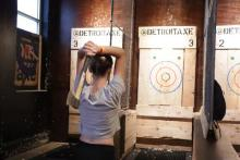 Photo of Jessica Schrader throwing an axe at Detroit Axe