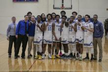 Henry Ford College men's basketball team celebrating after winning against St. Clair College