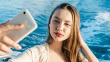 Image shows a young woman taking a selfie