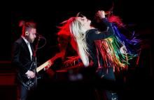 Image of Kesha performing and a guitar player behind her