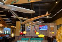 Photo of Longboard's interior decor, including surfboards hanging from the ceiling and a vibrant setting