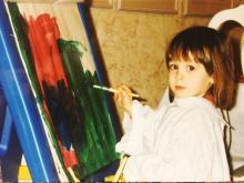 Toddler Elizabeth Moosekian paints dark broad strokes on a canvas.